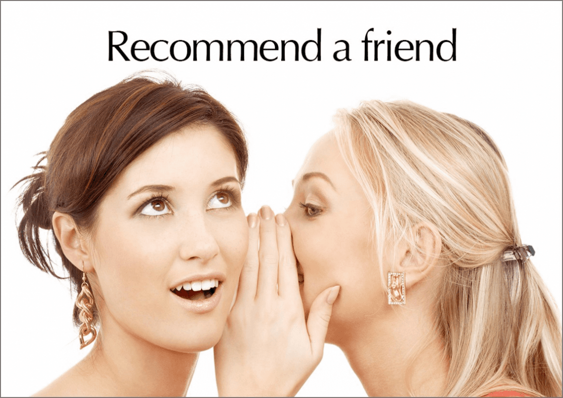 One young lady whispering to another young lady with Recommend a Friend written in text