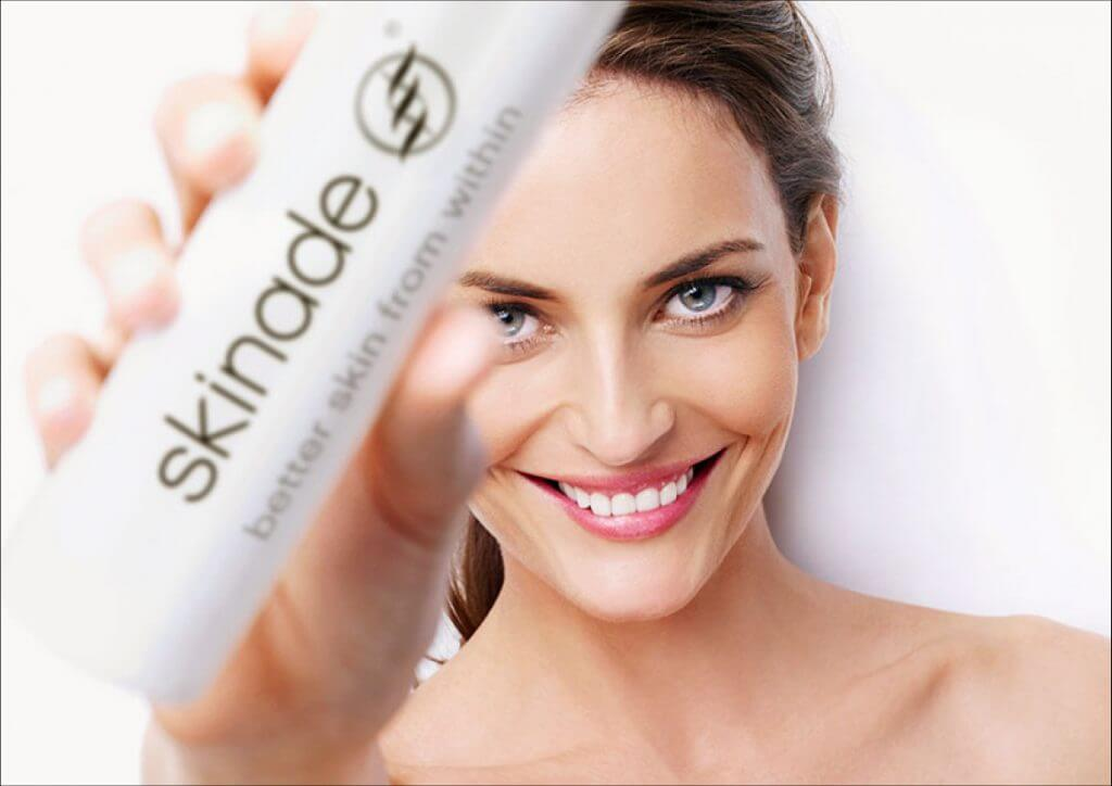 model holding a bottle of skinade treatment