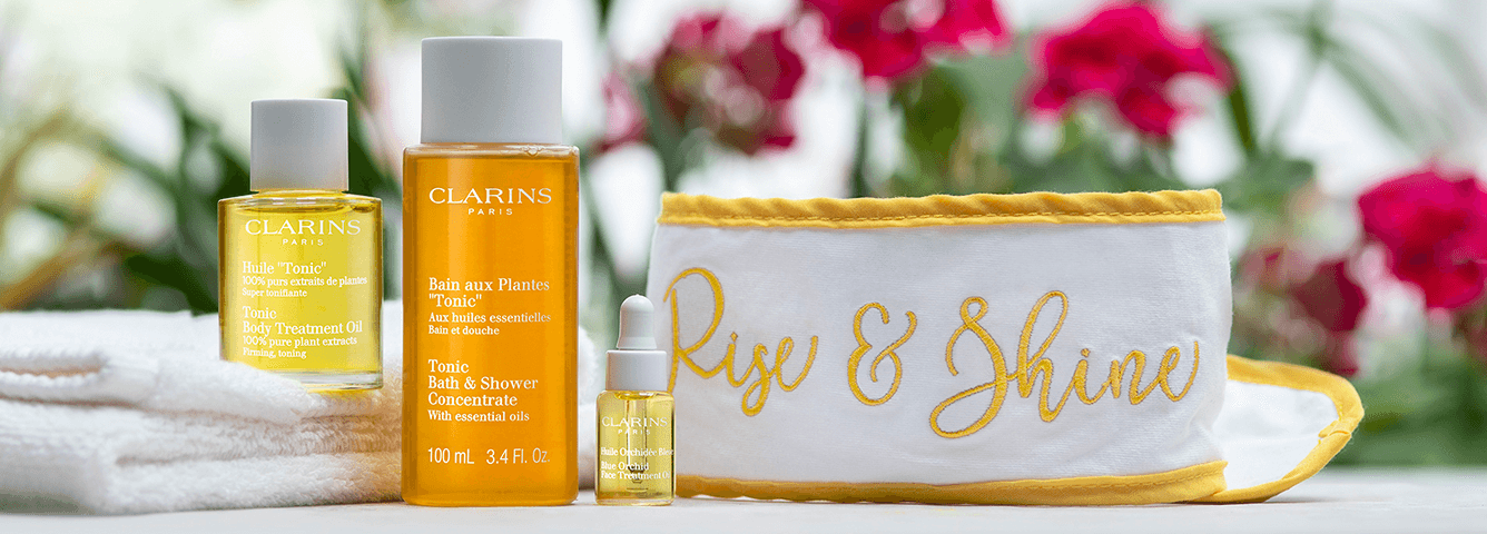clarins rise and shine headband pictured with three bottles