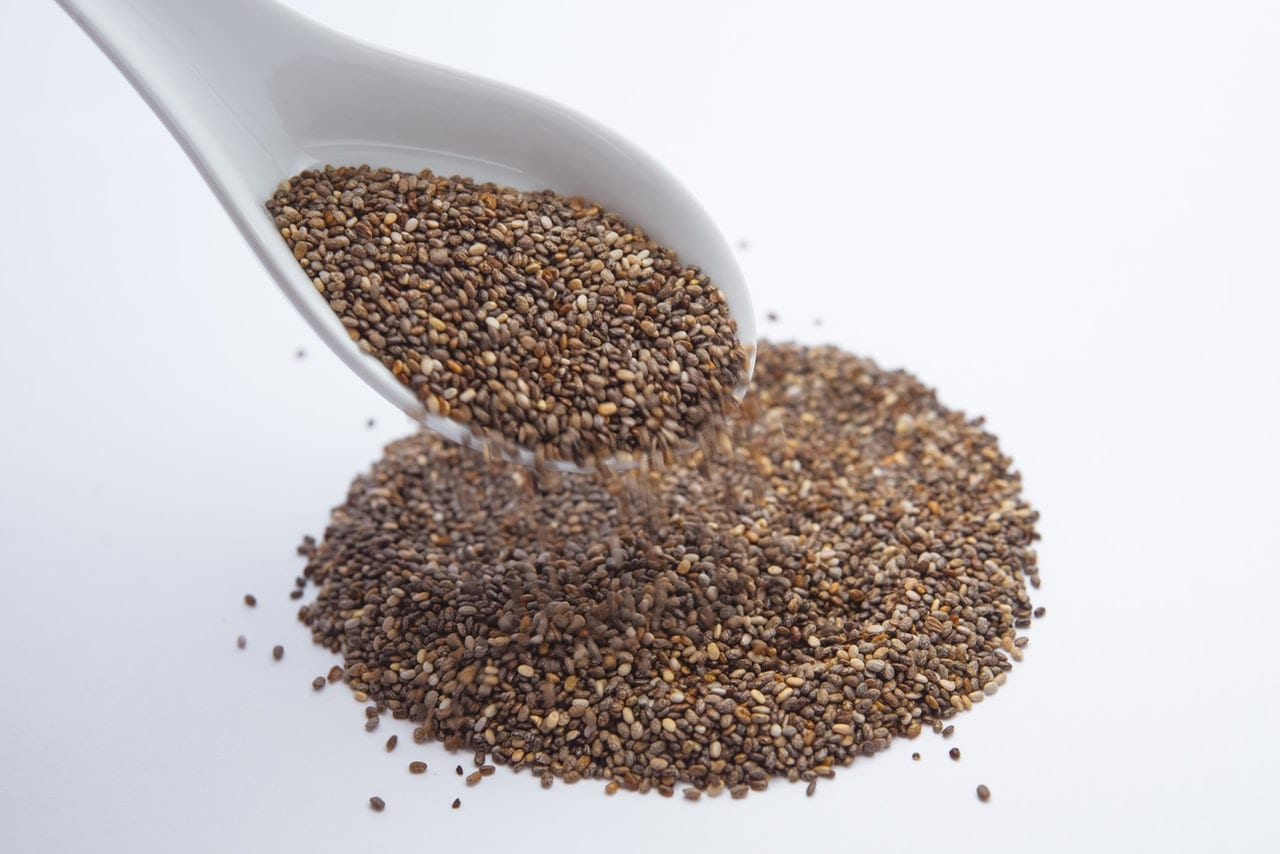Chia Seeds On A White Spoon And Spilling Onto The Counter Top