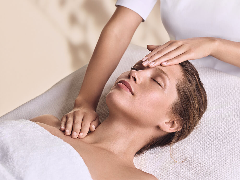 Lady relaxing during a facial with therapists hand on her forehead