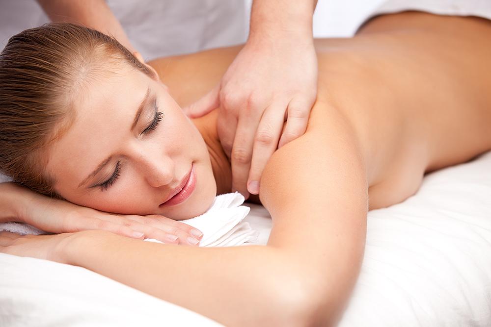 lady having a back massage lying on a towel